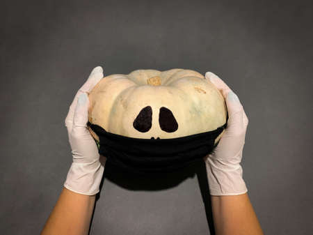 Top view of Halloween pumpkin in black protective medical mask holded on hands with gloves. Black background, Copy space