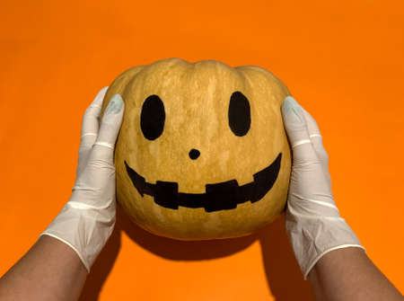 Hands in gloves holding orange pumpkin with Halloween painted face