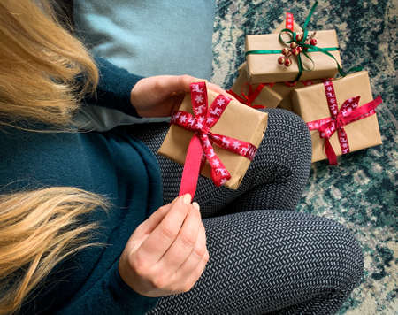 High angle close up on woman opening christmas present box with more gifts on background