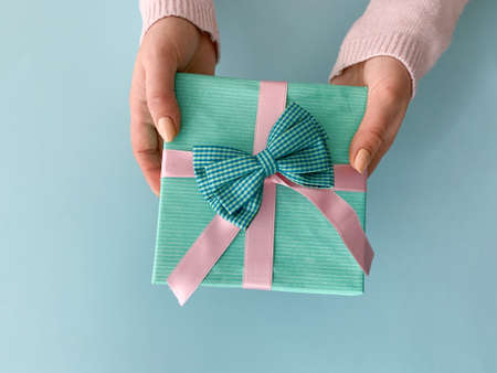 Female hands holding beautiful turquoise present with soft silk pink ribbon over light blue background.