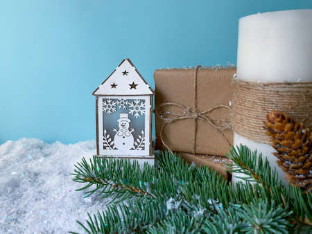 Winter decorated lantern with snowman next to presents, white candle and fir tree branch. Christmas  holiday composition with snow. Stock Photo