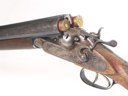 gun shell: old shotgun and red cartridges on white background