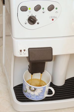 percolate: A cup at the ready in an expresso machine. Stock Photo