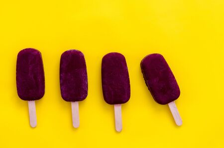 Homemade blueberry ice pop on the yellow