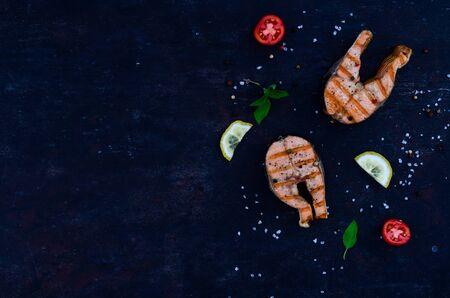 group salmon steaks pepper salt top view on dark background