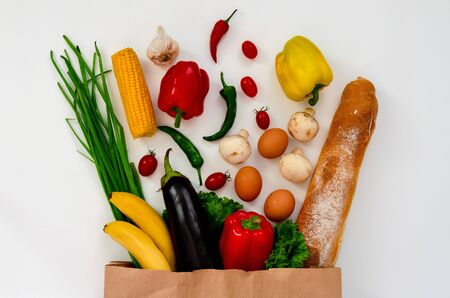 Healthy food background. Healthy food in full paper bag of different products on white background.