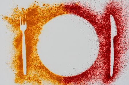 Spicy card made of hot spices, spoons, forks in turmeric, paprika on a white background Фото со стока - 129774073
