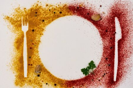Spicy card made of hot spices, spoons, forks in turmeric, paprika on a white background Фото со стока - 129774095