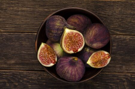 figs in a rustic ceramic bowl on the dark wooden