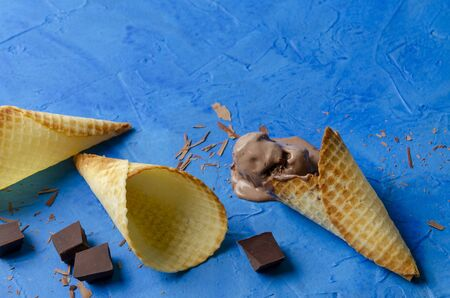 Traditional waffle cones for ice cream on blue wooden background. Summer, open space Wafers and chocolate chips in Фото со стока