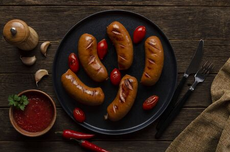 grilled sausages on the black plate on the wooden background.