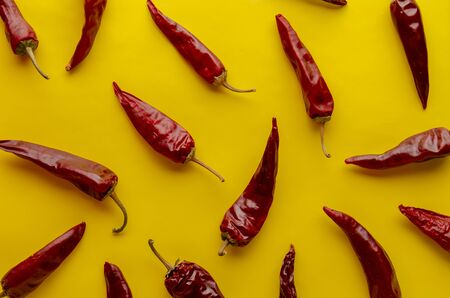 Red chilli peppers on yellow background.