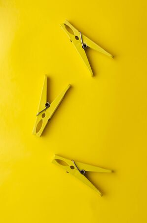 Wooden and yellow clothespins on yellow