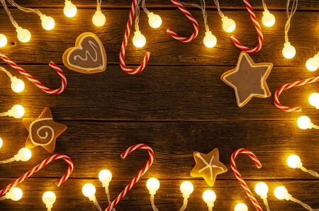 Christmas background. Gingerbread cookies, christmas candy and holiday decorations frame on wooden boards. Top view with copy space for text