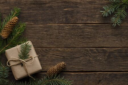 Christmas gifts with fir tree branches on wooden background, copy space