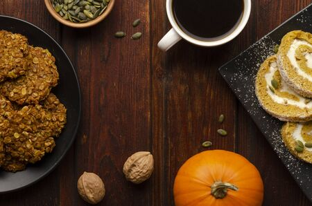 Pumpkin Roll and pumpkin cookies on the wooden table with cup of coffee. Holiday