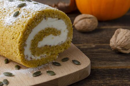 Pumpkin Roll with powdered sugar with walnuts and pumpkin Фото со стока