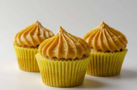 Cupcakes de calabaza con crema de caramelo de calabaza aislado en un blanco