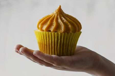 children hand holding pumpkin cupcakes with pumpkin-caramel cream Isolated on a White Background