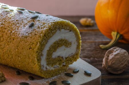 Delicious Pumpkin Roll with powdered sugar with walnuts and pumpkin Фото со стока