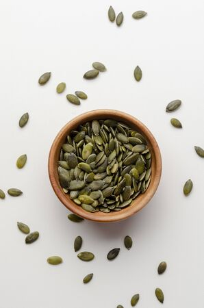 pumpkin seeds in a wooden bowl on a white