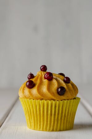 Pumpkin cupcakes with pumpkin-caramel cream and lingonberry on wooden
