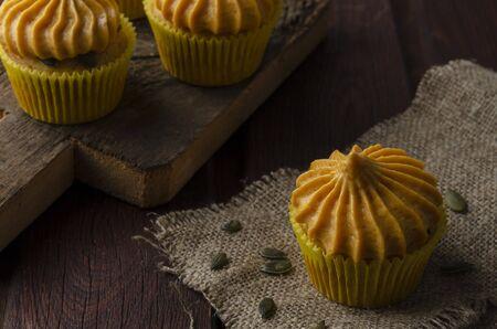 Pumpkin cupcakes with pumpkin-caramel cream wooden