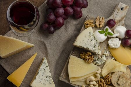 cheese plate on the wooden background with jam nuts