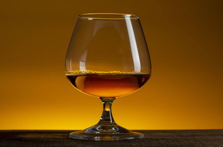 glass of Calvados Brandy and red apples on wooden