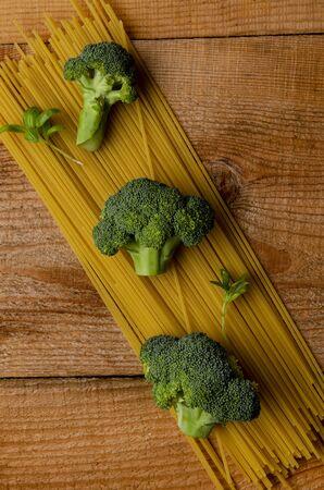 Ingredients for italian pasta. Spaghetti, broccoli, parmezan on wooden