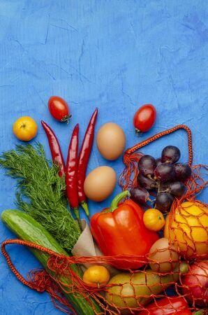 mesh bag with different food on the color background. Reklamní fotografie
