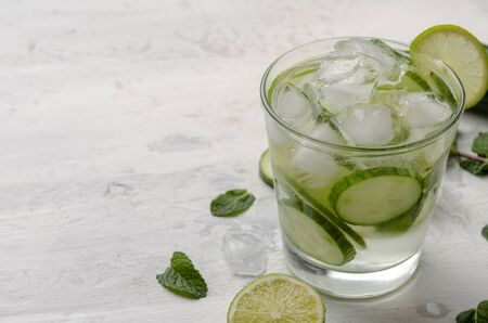Aufgegossenes Wasser auf einem Glas. Detox Wassermischung aus Gurke