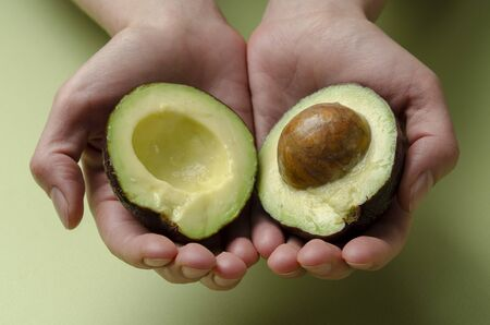 avocado in a hand of woman Isolated on colored Stock fotó