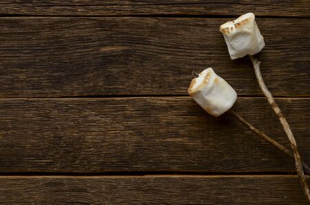 Marshmallow on the stick on wooden back