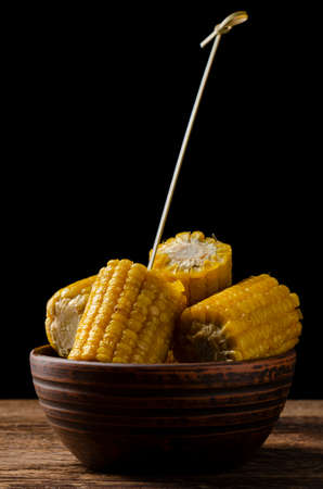Fresh roasted or grilled corncobs served on a bowl on black background