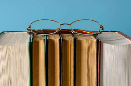 books with glasses on colored background. International literacy Day