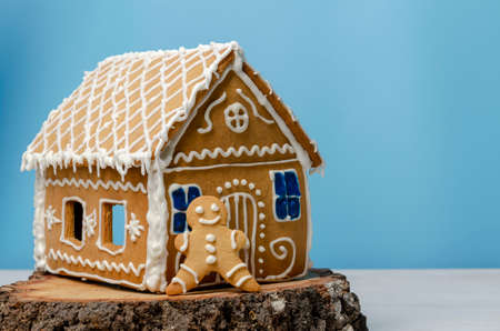 Christmas gingerbread house and man on blue