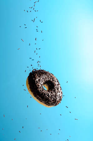 Flying in the air donut with chocolate on a blue background. Levitation Stockfoto