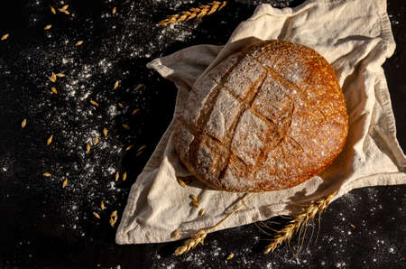 Gold round loaf of rustic bread and ears of wheat. Black background. 免版税图像