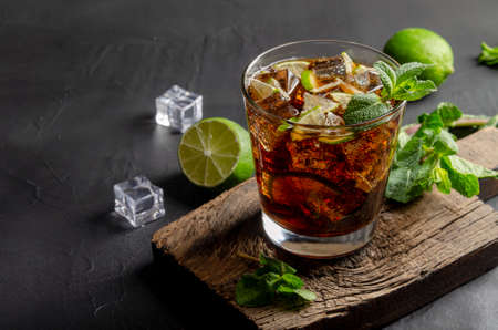 cuba libre, rum and cola cocktail in glass with a lime and mint on black background 免版税图像