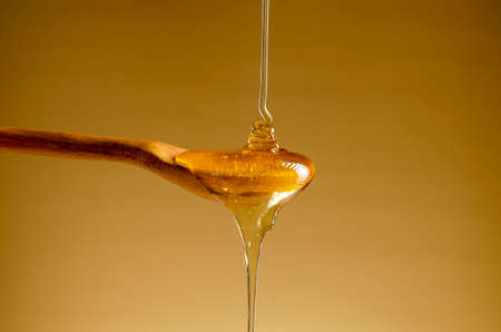 Spoon with a pouring drop of golden honey on yellow background. 免版税图像