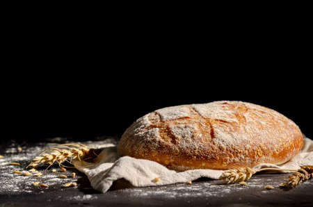 Gold round loaf of rustic bread and ears of wheat. Black background. space for text. 免版税图像