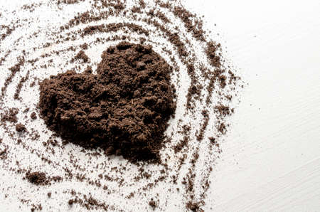 Heart shaped dry soil on white wooden background. Earth day concept.