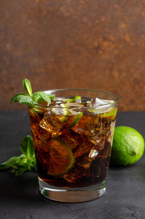 cuba libre, rum and cola cocktail in glass with a lime and mint on black