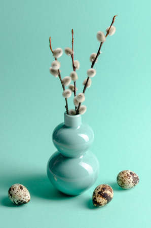 Vase with a willow on a table with quail eggs. Easter, spring concept