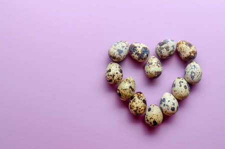 Quail eggs in the shape of a heart. Quail eggs on violet background 免版税图像