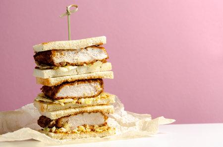 Katsu sandos japanese sandwich with chicken or pork chop, cabbage and tonkatsu sauce isolated on pink background. 免版税图像