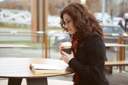 a very pretty woman attentively reads a book over a Cup of hot drink on the terrace of a street cafe Standard-Bild