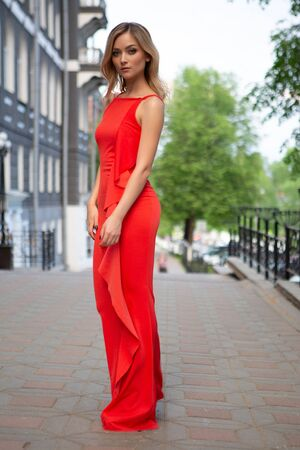 a beautiful blonde woman in an elegant red evening dress stands on a deserted city street