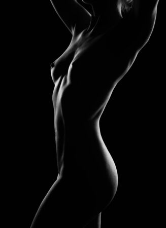 photo of a light outline of a perfect Nude female body on a dark background. A naked girl with a magnificent figure straightens her luxurious hair Archivio Fotografico